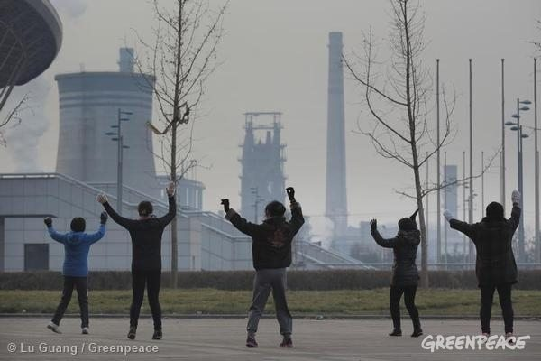 Local women dance together with their backs to the Handan Stadium facing the Wen'an steel plants. These women come here every day at the same time. Wu'an is home to dozens of steel mills, power stations, and coking plants. Whatever the wind direction, the pollution is always choking. Air pollution has become one of the most severe environmental problems in mainland China. 12/03/2014 © Lu Guang / Greenpeace