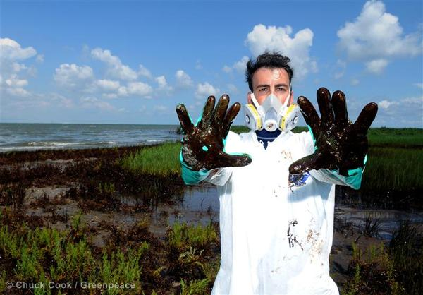 Greenpeace activist Joao Talocchi shows his hands covered in crude oil washed ashore on Casse-tete Island on the Louisiana gulf coast  near the site of the Deepwater Horizon disaster.