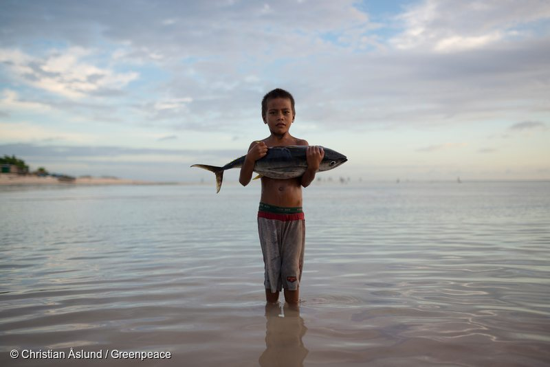 Boy with Tuna Fish Stands in Sea