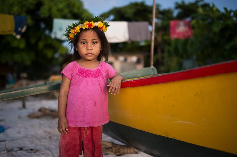 Little girl standing by a boat on a beach as the Pacific Island search for climate justice continues