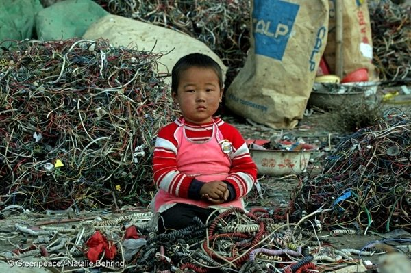 A small Chinese child sitting among cables and e-waste, Guiyu, China. Much of modern electronic equipment contains toxic ingredients. 8 March 2005.