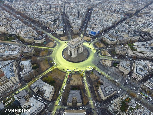 As the Paris climate conference enters the closing stretch, Greenpeace activists create a solar symbol around the world-famous Paris landmark, the Arc de Triomphe, by painting the roads yellow with a non-polluting water-based paint to reveal the image of a huge shining sun.