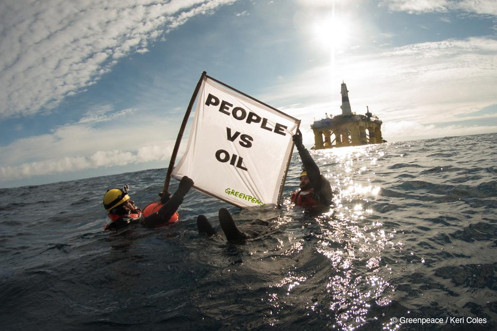 "Greenpeace activists in the water hold up a sign saying ""People vs Oil"" in front of an offshore oil rig."