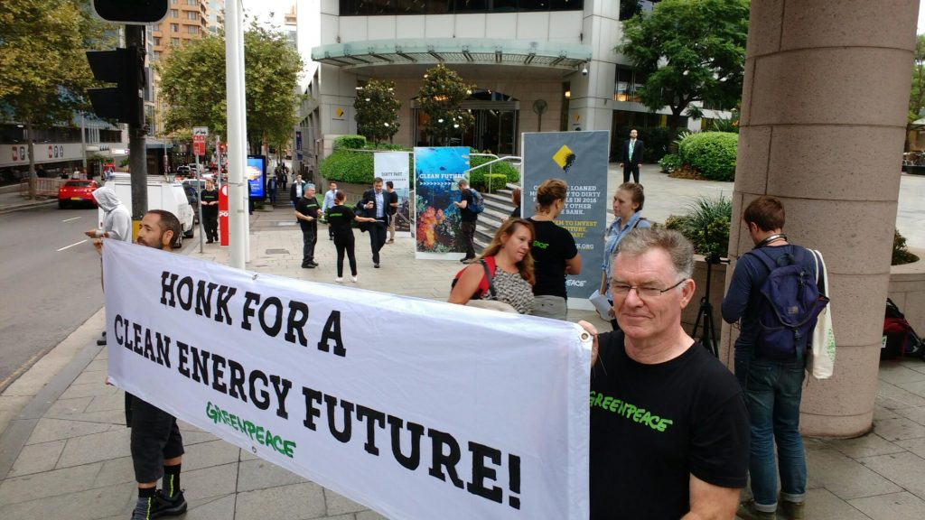 Volunteers outside CommBank HQ hold a sign saying 'Honk for a clean energy future!'