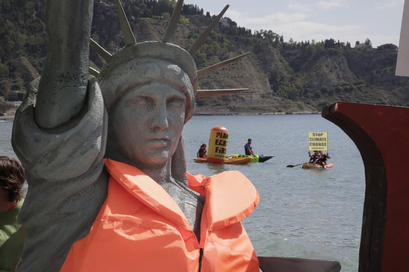 At the Giardini Naxos beach in Taormina, Greenpeace activists unveil a four-meter-high Statue of Liberty replica covered with a life jacket to symbolise the threat that climate change and rising seas pose.  In the water, activists in kayaks unfurl flags and banners with the message 'Planet Earth first'.     Greenpeace is calling on the G7 leaders to rapidly implement the Paris Climate Agreement, a generation-defining pact signed by nearly 200 countries, and to resolutely move forward despite the threats of US President Trump to abandon the agreement.