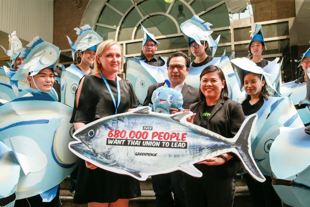 "Dr. Darian McBain, Group Director of Sustainable Development for Thai Union, receives a tuna placard on which is written ""Over 680,000 people have signed petitions calling for a more sustainable and ethical tuna industry."