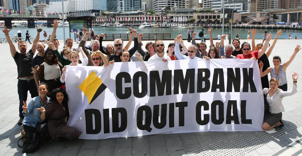 """Supporters gather around a banner saying """"Coalbank did quit coal,"""" outside Commbank's 2017 AGM. The movement called on Australia's remaning 3 big banks NAB, ANZ and Westpac to ditch coal too."""