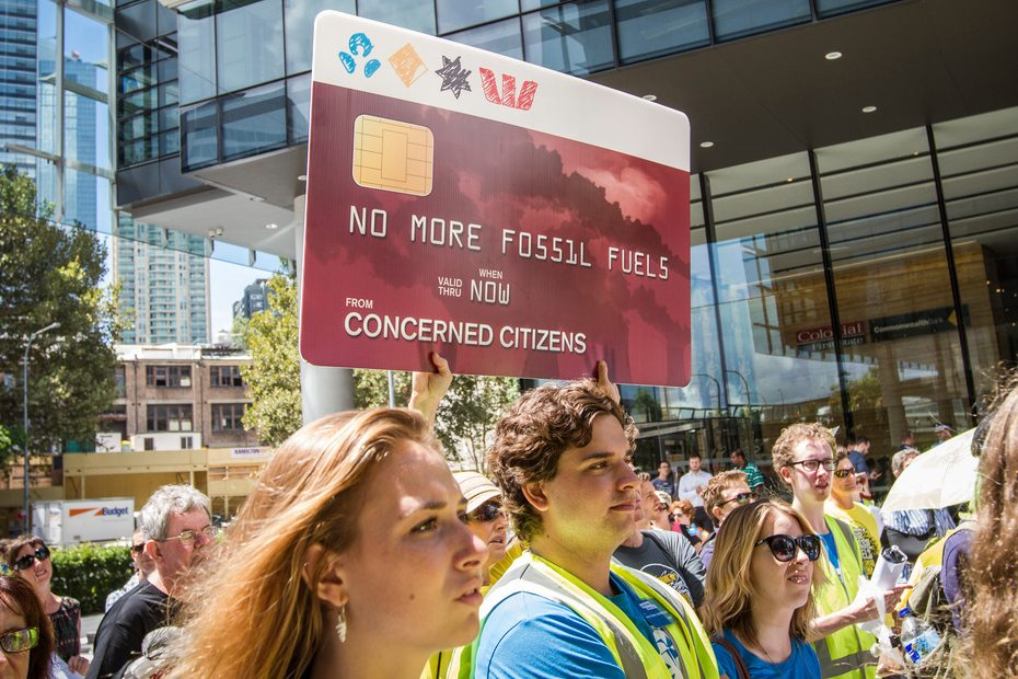 """At a Global Divestment Day rally, supporters hold up a bank-card shaped sign with the logo's of Australia's big four banks - ANZ, Commbank, NAB and Westpac - and the following message """"No more Fossil Fuels"""" - """"Concerned Citizens""""."""