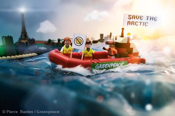 Greenpeace activists place Lego mini figures to protest with banners reading: 'Save the Arctic' against Shell in Paris.