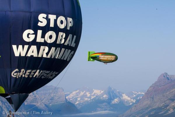 """The Greenpeace thermal airship A.E. Bates flies by Glacier National Park near St. Mary's. The airship flew with banners reading, """"Coal exports fuel climate change"""" and """"Keep our coal in the ground"""" to highlight the risks of coal export and mining."""