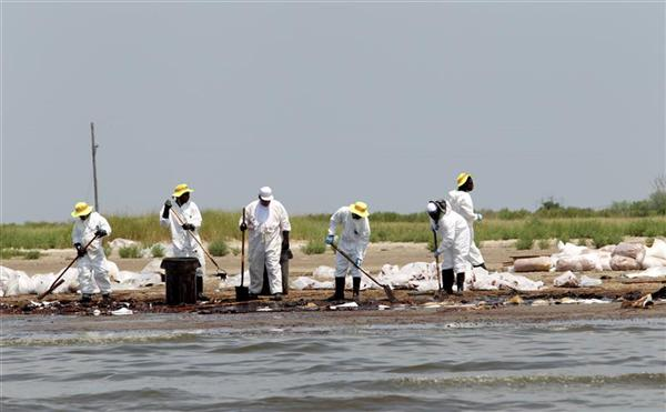 Workers try to remove oil from the Deepwater Horizon wellhead off the beach in Grand Terre Isle in Barataria Bay.