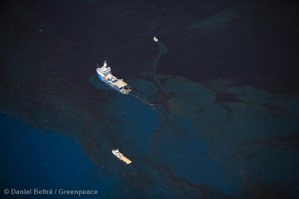 Ships are dwarfed by the amount of oil on the surface of the ocean as they work to contain the oil near the site of the Deepwater Horizon disaster in the Gulf of Mexico.