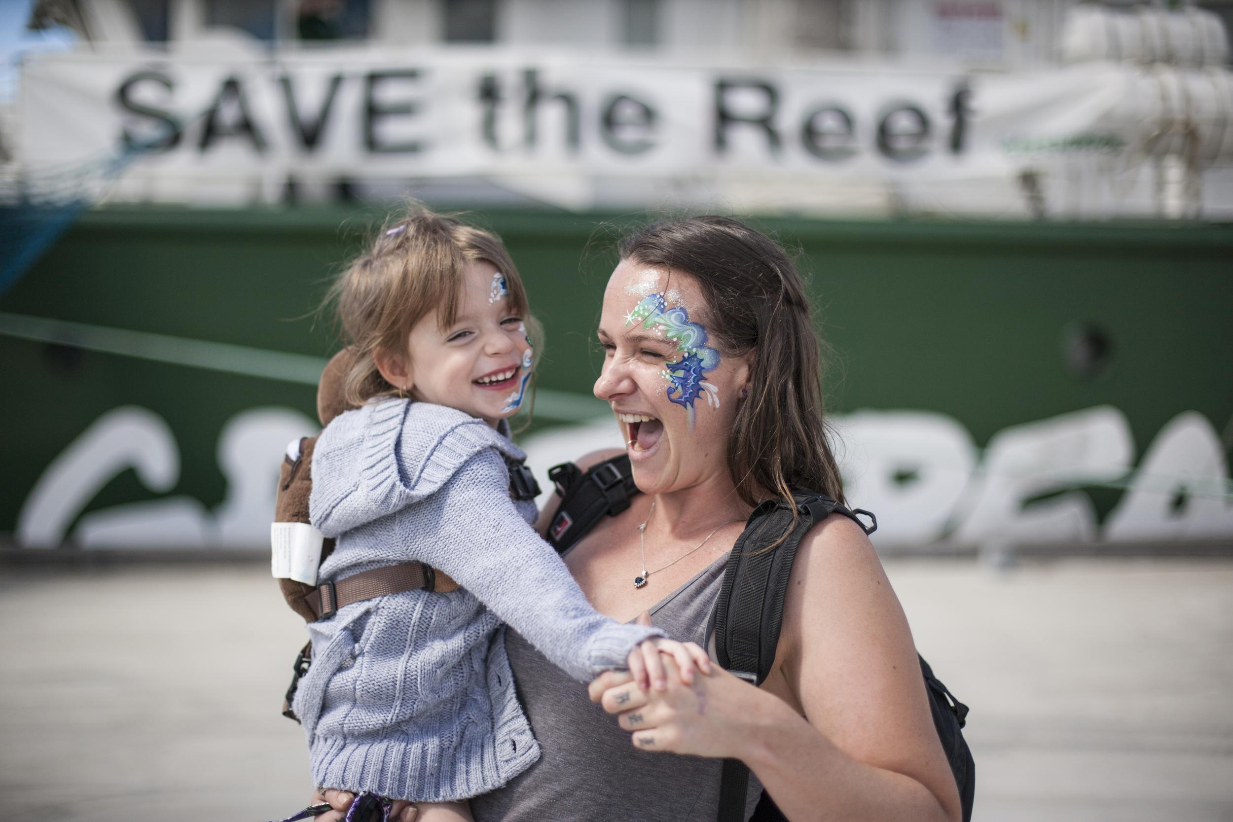 Mother with her child in front of the Rainbow Warrior