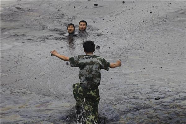 A man attempts to rescue two oil firefighters, Zhang Liang and Han Xiaoxiong, struggling in thick oil slick. One man Zhang Liang (top L) later died as he drowned in the thick oil. The workers ran into trouble as they were attempting to fix an underwater pump during oil spill cleanup operations. The spill was caused by a pipeline blast at the Dalian Port.