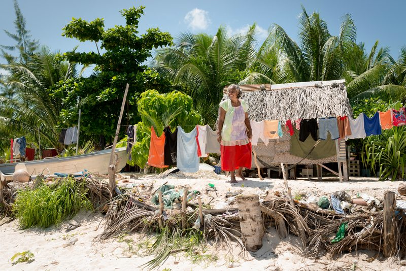 A woman outside of her home in a fishing village near Betio in Kiribati