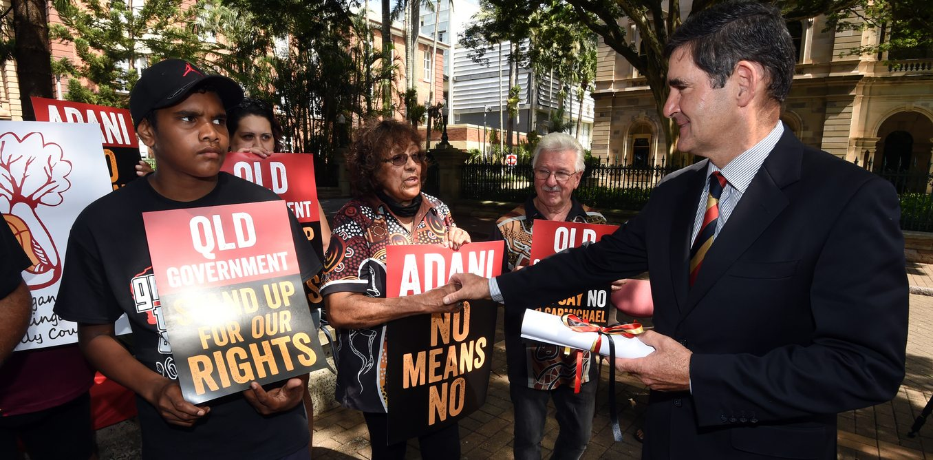 Queensland's Speaker of the House Peter Wellington holds a Declaration of Defence of Country given to him by the Wangan and Jagalingou people (W&J) outside Parliament House in Brisbane, Thursday, March 26, 2015. The W&J people have announced that they have refused Indian conglomerate Adani and the QLD government a Land Use Agreement for the Carmichael coal mine, the biggest in Australian history, on their traditional lands. (AAP Image/Dan Peled) NO ARCHIVING