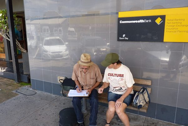 Claire talks to a local outside the Commonwealth Bank who signs the petition calling on them to stop funding coal.