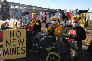 """Community members in Newcastle, New South Wales, Australia, hang out coal-covered clothes and display signs reading """"No new mines"""" and """"No New Coal"""" to highlight the serious health and climate impacts of the Commonwealth Bank's lending policies. At the same time in Newcastle port Greenpeace activists occupy the world's largest coal port with the message """"CommBank's Coal Kills""""."""