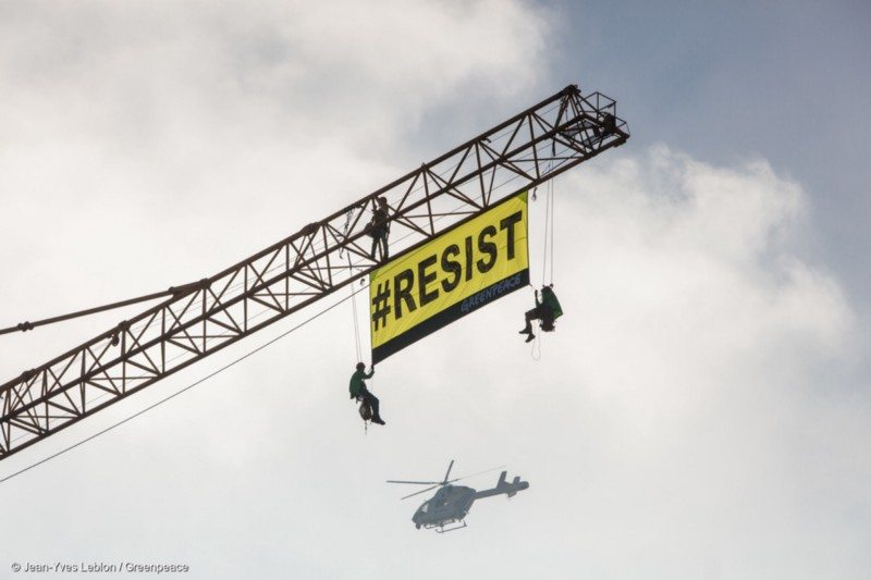 On a crane in front of the US Embassy, 5 activists from Greenpeace Belgium put a banner saying RESIST while Trump is in Brussels visiting the NATO