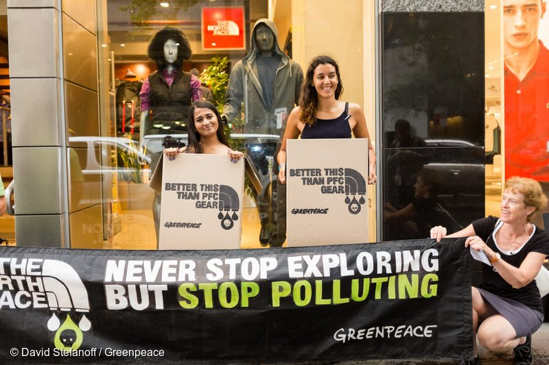"Greenpeace activists display a banner ""Never Stop Exploring But Stop Polluting"" while wearing cardboard boxes reading ""Better This Than PFC Gear"" outside the North Face store in Sydney. They highlight the company's continuous failure to eliminate hazardous chemicals like PFCs (poly- and per-fluorinated compounds) from their weatherproof products."