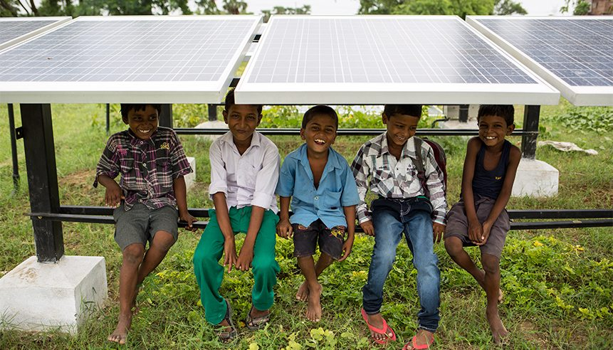 Children sit under solar panels at Bishunpur Tolla, Dharnai village. A solar-powered micro-grid is now supplying electricity to the village. © Vivek M. / Greenpeace
