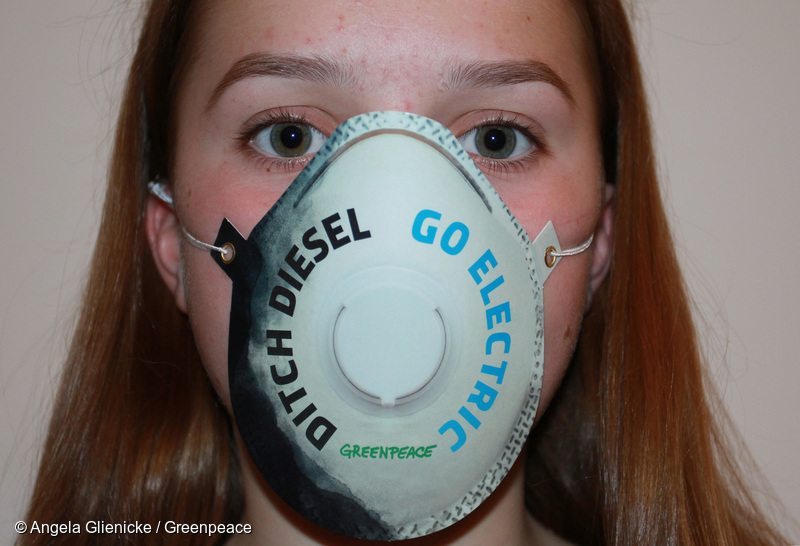 Teenage girl wearing air pollution mask saying ' ditch diesel, go electric'.