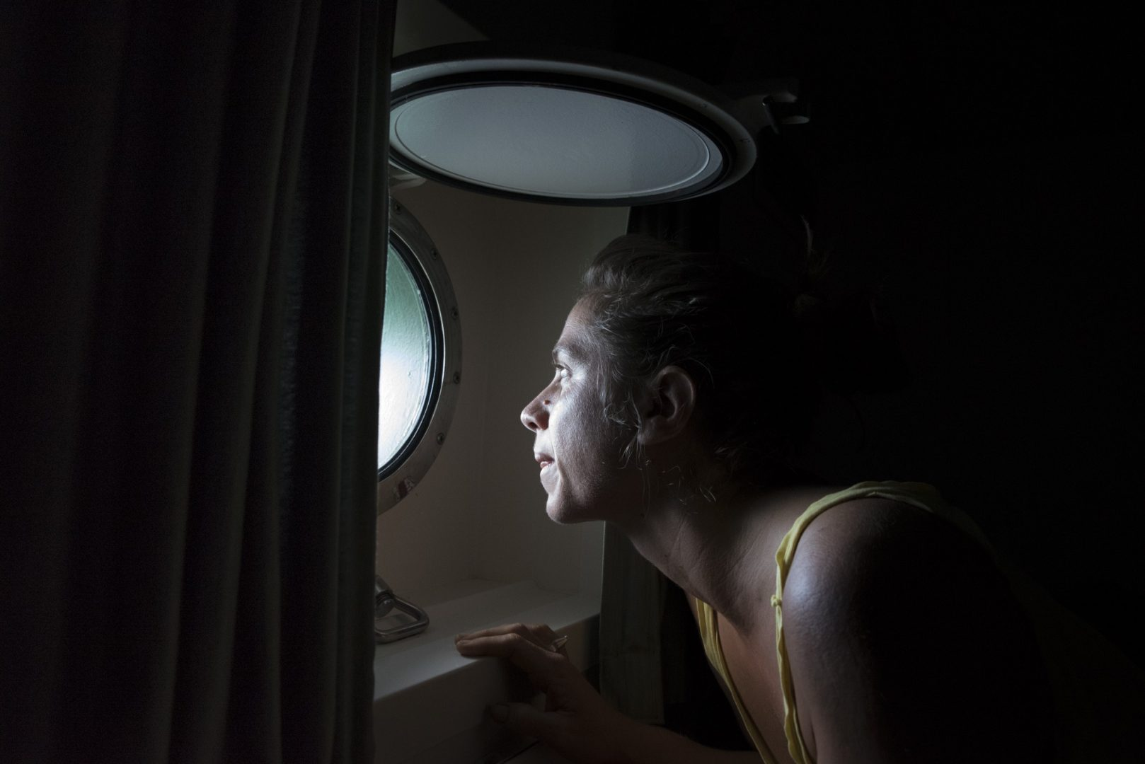 Rainbow Warrior III cook Laurence Nicoud wakes and checks the weather from her cabin.