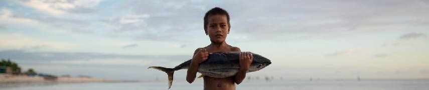 A kid holding a bigeye tuna in a Pacific island.