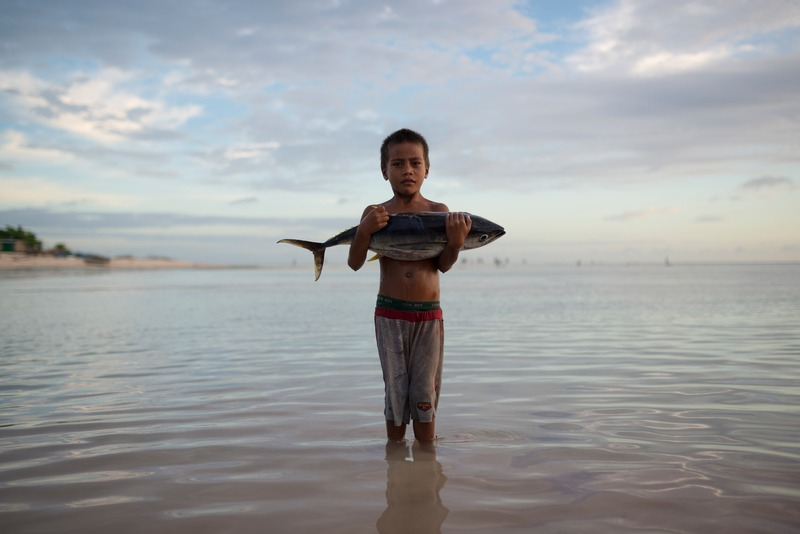 A kid on in an island of the Pacific holds a yellowfin tuna. Fishing in the ocean is the main food supply for most of these communities
