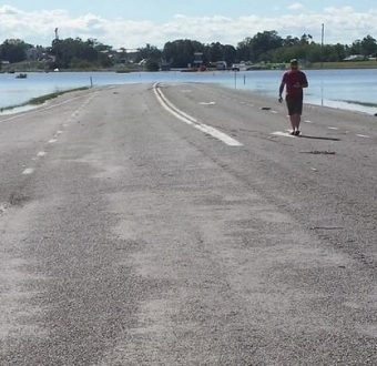 Road with person walking on it and floodwaters