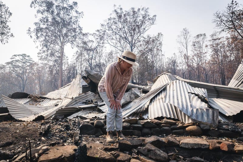 Bushfire survivor Melinda Plesman examines the remains of her destroyed property in Nymboida, New South Wales