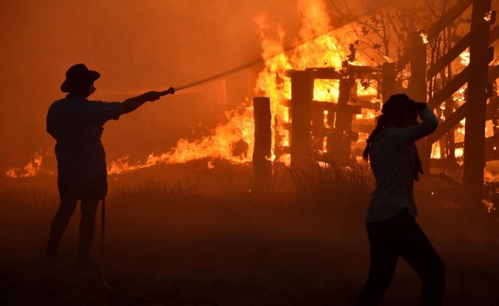 Residents defend a property from a bushfire at Hillsville near Taree