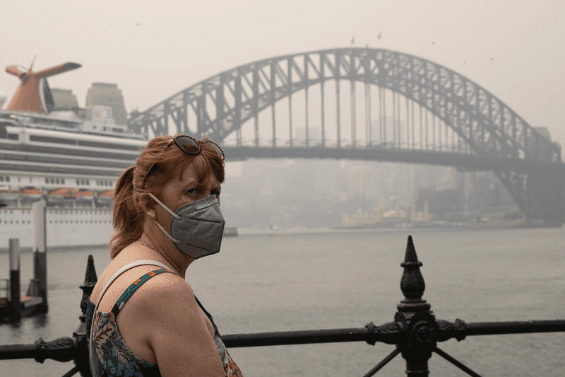 A woman wears a mask in Circular Quay in Sydney CBD due to poor air quality index